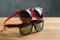 Red and black sunglasses on a table Stock Photo
