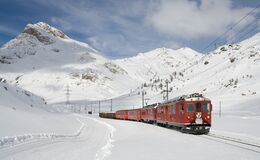 Red and Black Train Running Along Snow Covered Field Royalty Free Stock Images