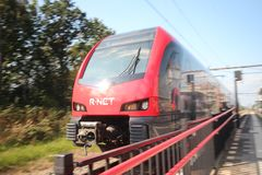 Red and black train on station Waddinxveen of R-NET, a light rail train between alphen and gouda. In the Netherlands stock photography
