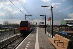 Red and black train on station Waddinxveen Triangel of R-NET, a light rail train between alphen and gouda. In the Netherlands stock photo