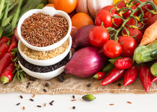 Red, black and unpolished organic rice and vegetables Stock Image