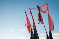 Vintage flags under a blue sky. Red and black vintage flags under a blue sky Stock Photos