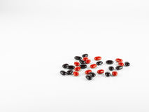 Red and black Vitamin Pills . Royalty Free Stock Photos