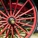 Red and black wagon wheel and chain. Detail of wheel on antique motor driven vehicle royalty free stock images