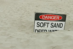 Red, black and white Danger, Soft Sand, Deep Water sign on the beach Stock Image