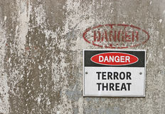 Red, black and white Danger, Terror Threat warning sign. On industrial background Stock Image