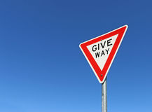 Red, black and white give way road sign in a bright blue sky Royalty Free Stock Photo