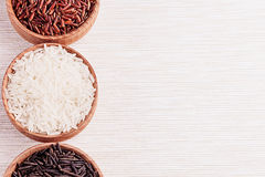 Red, black and white rice close-up in wood bowls on beige fabric. Rice texture background Royalty Free Stock Image