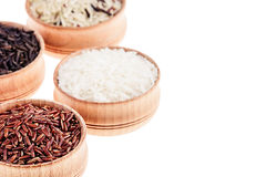 Red, black and white rice close-up in wood bowls on white background. Isolated. Rice texture background Stock Photo