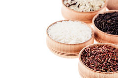 Red, black and white rice close-up in wood bowls on white background. Isolated. Rice texture background Stock Photos