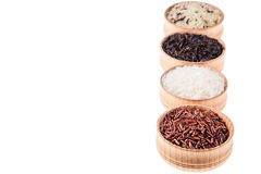 Red, black and white rice close-up in wood bowls on white background. Isolated. Rice texture background Stock Images