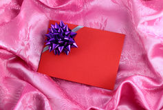 Red blank gift card with ribbon. On pink satin Stock Photos