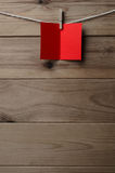 Red Blank Greetings Card Pegged to String on Wood Background. A blank, red greetings or Christmas card, pegged to string against old wood planked background stock image