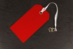 Red blank old paper cloth tag or label isolated on a dark slate background. Close up stock photography