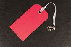 Red blank old paper, cloth tag or label, isolated on a dark slate. Red blank old paper, cloth tag or label, isolated on a dark slate in the background. Close up royalty free stock images
