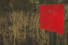 Red blank rectangular sign in the crop field with copy space to stock image