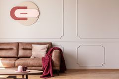 Red blanket and pink cushion on sofa in white apartment interior with poster and table. Real photo royalty free stock images