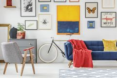 Red blanket thrown on blue settee in bright sitting room interior with patterned armchair, bike and many posters hanging on the w. All stock photos