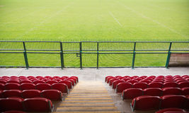 Red bleachers looking down on football pitch Stock Photo