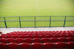 Red bleachers looking down on football pitch Royalty Free Stock Photo
