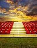 Red bleachers with sunset sky. Background royalty free stock images