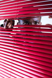 Red blinds. Afro-american businessman glancing through red blinds. Copy space Stock Photos