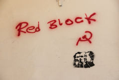Red block graffiti on a wall. Political graffiti and stencil in red and black on a light brown wall Stock Photo