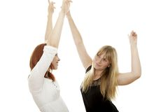 Red and blond haired girls dance with arms in air Royalty Free Stock Images
