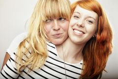 Red and blond haired girls friend laughing and hug Stock Photos