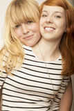 Red and blond haired girls friends laugh and hug Royalty Free Stock Images