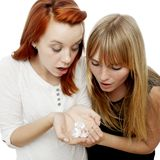 Red and blond haired girls gape about diamonds. Young beautiful red and blond haired girls in front of white background Stock Image