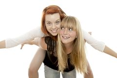 Red and blond haired girls have fun piggypack Royalty Free Stock Photography