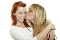 Red and blond haired girls kissing cheek. Young beautiful red and blond haired girls in front of white background Stock Photos