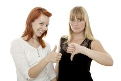 Red and blond haired girls thumb up and down royalty free stock photos