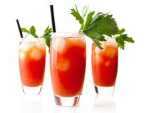 Red Bloody Mary drinks with ice cubes with celery isolated on white. Background royalty free stock images
