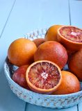 Red (bloody) oranges in basket. Red (bloody) oranges in blue basket on blue wooden table Royalty Free Stock Image