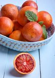 Red (bloody) oranges in basket. Red (bloody) oranges in blue basket on blue wooden table Royalty Free Stock Photography