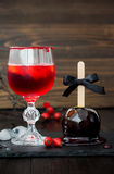 Red bloody vampire cocktail and black poison caramel apple. Traditional dessert recipe for Halloween party. Royalty Free Stock Photography