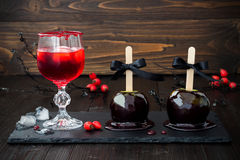 Red bloody vampire cocktail and black poison caramel apples. Traditional dessert recipe for Halloween party. Stock Photos