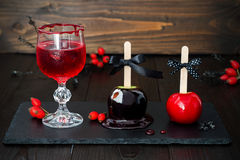 Red bloody vampire cocktail and black poison and red caramel apples. Traditional dessert recipe for Halloween party. Stock Photography