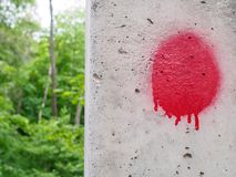 Red blot with smudges on a concrete pillar in spring wood royalty free stock image