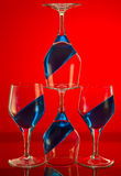 Red and Blue. A close up of five wine glasses with blue sloping contents set against a red background royalty free stock photography