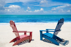Red and blue beach chairs near ocean. Summer background Stock Image