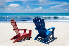 Red and blue beach chairs near ocean. Summer background Royalty Free Stock Image