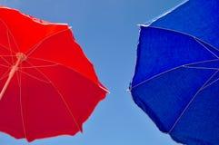Red and blue beach umbrella and blue sky above Stock Photos
