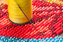 Red and blue beads with needle and thread Royalty Free Stock Photo