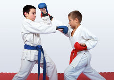 With a red and a blue belt athletes doing paired exercises  karate. With a red and a blue belt sportsmen doing paired exercises  karate Stock Photo