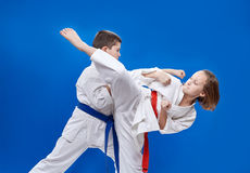With red and blue belt the children are beating  karate blows Stock Photo