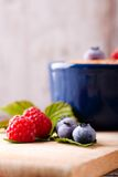 Red and blue berries on chopping board Stock Photography