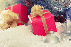 Red and blue boxes with gold ribbon in snow  under pine tree Stock Image